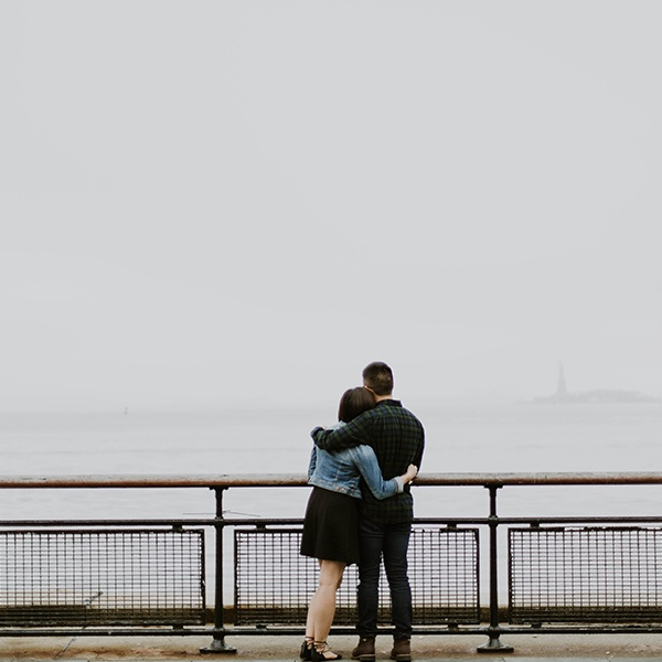 A couple standing with their arms around each other at the New York City waterfront with the Statue of Liberty visible in the distance through the haze.